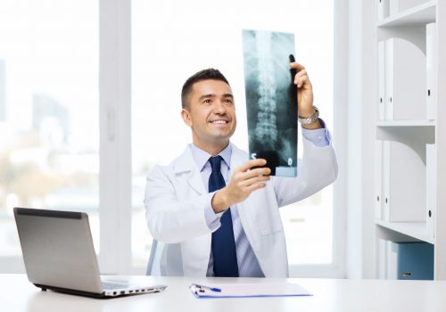 healthcare, technology, rontgen, people and medicine concept - smiling male doctor in white coat with laptop computer looking at x-ray in medical office