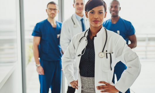 54832373 - black female doctor in charge at hospital, leading medical team om doctors and surgeons