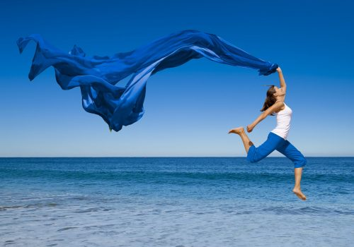 9209652 - beautiful young woman jumping on the beach with a colored tissue
